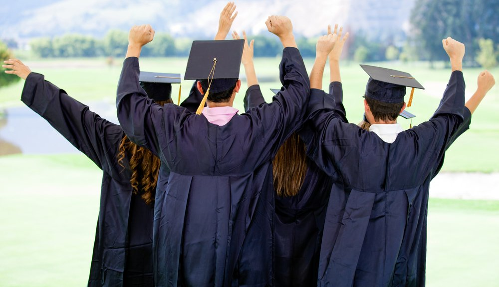 Excited group of people on their graduation day with arms up